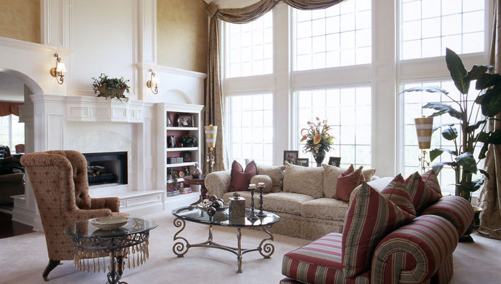 Cathedral ceilings and large window bring natural light to a graceful and stylish living room. The custom drapery accents the large windows. The furniture from Swaim, glass and brass tables, custom mill work, and flambeau lighting create a cozy conversation spot.