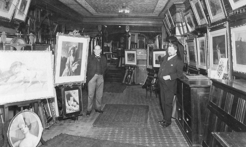 Black and white photo of Charles and John Kraushaar in front of framed art