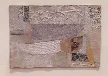 Collage of various pieces of white, grey, yellow textured paper