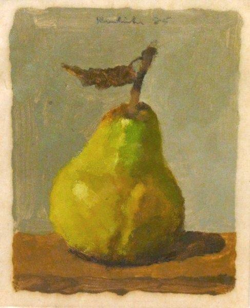 Green/yellow pear on brown surface with blue background
