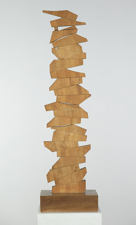 Vertical wood sculpture with asymmetrical pieces jutting out
