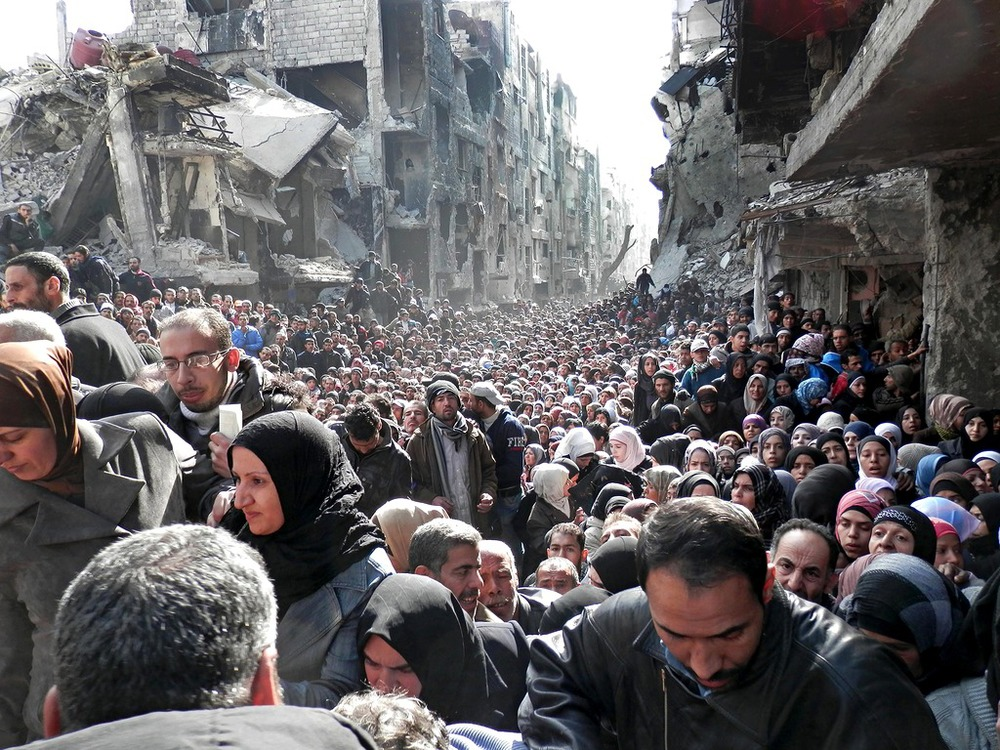 Residents of Yarmouk Camp in Damascus queue for food aid distributed by UNRWA on January 31, 2014.