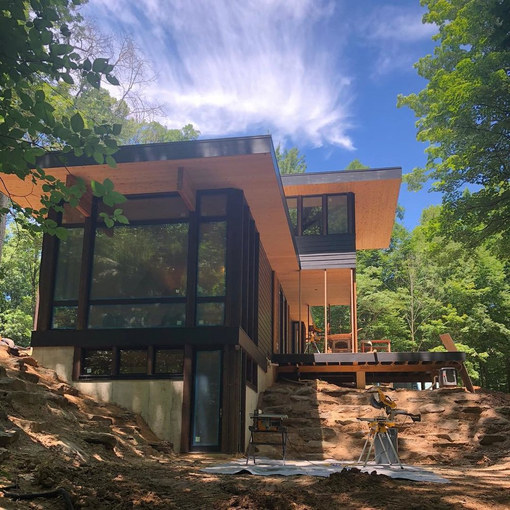 MICHIGAN SUMMER DAYS AHEAD  Dreamy clouds linger over this modern cottage nestled in a grove of trees.
