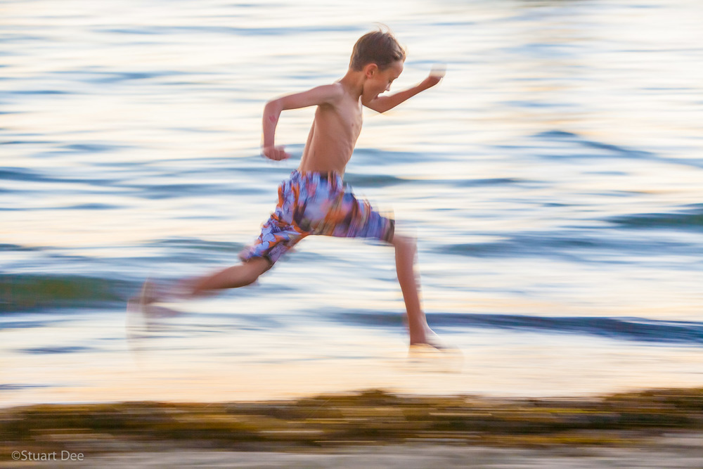 Young boy running along the beach at sunset,  Vancouver, BC, Canada