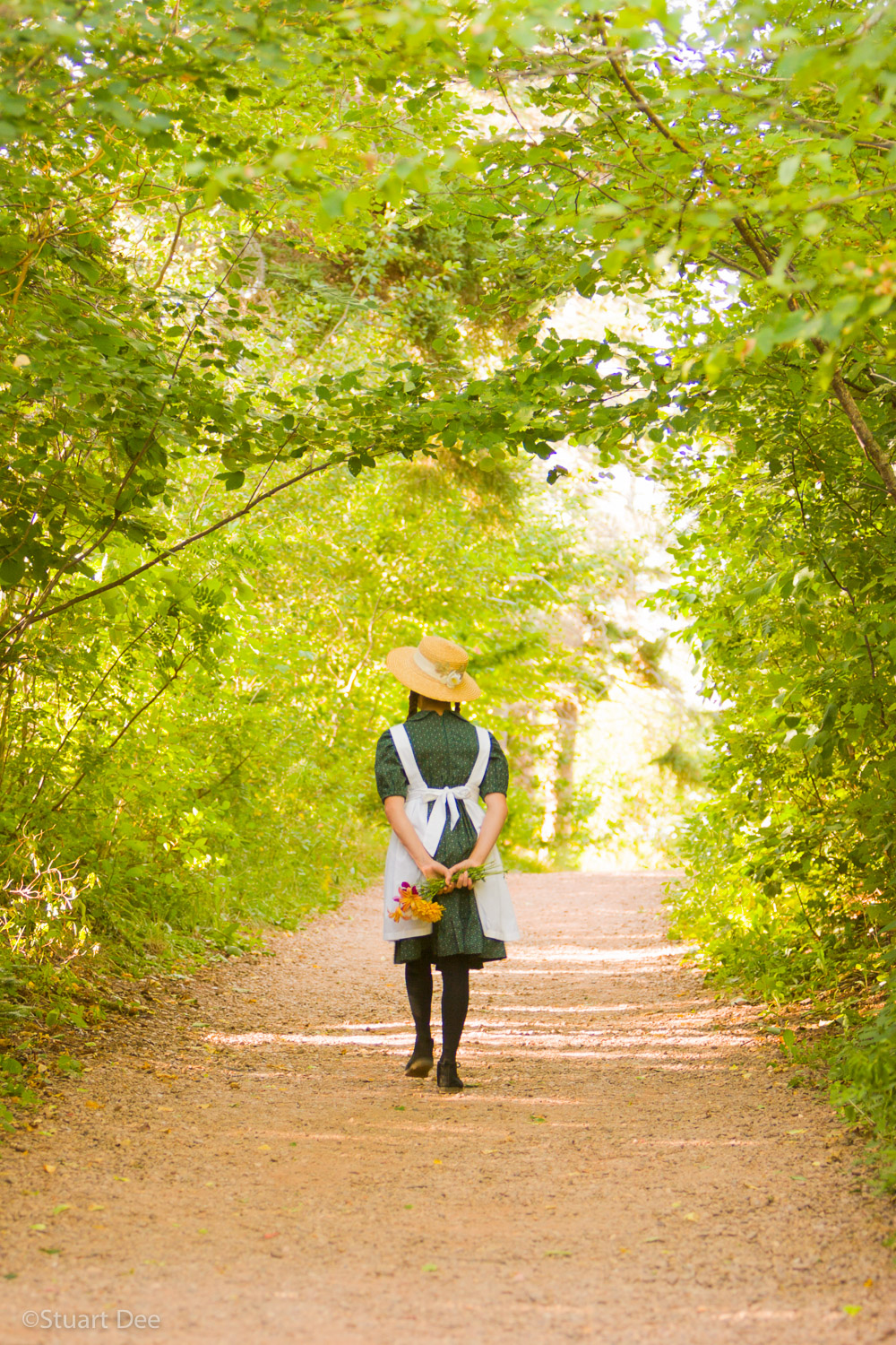 "Young girl with hat and braids, ""Anne of Green Gables"", walking through Lovers' Lane, by the Green Gables home, Cavendish, Prince Edward Island, Canada