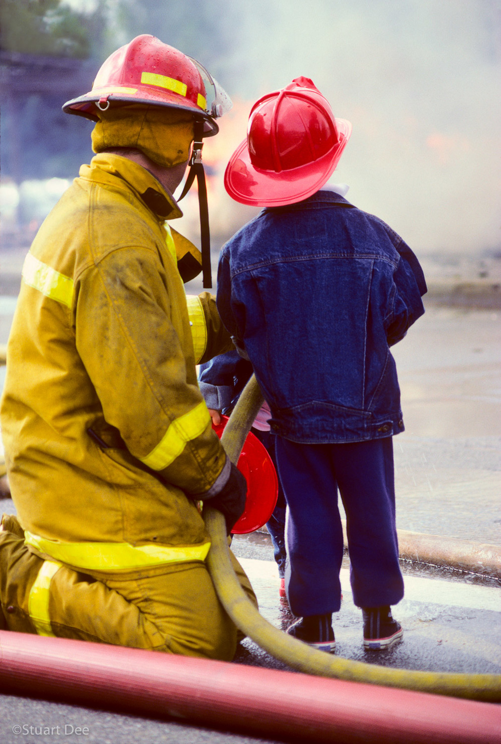 Young boy watching a fireman keep fire under control
