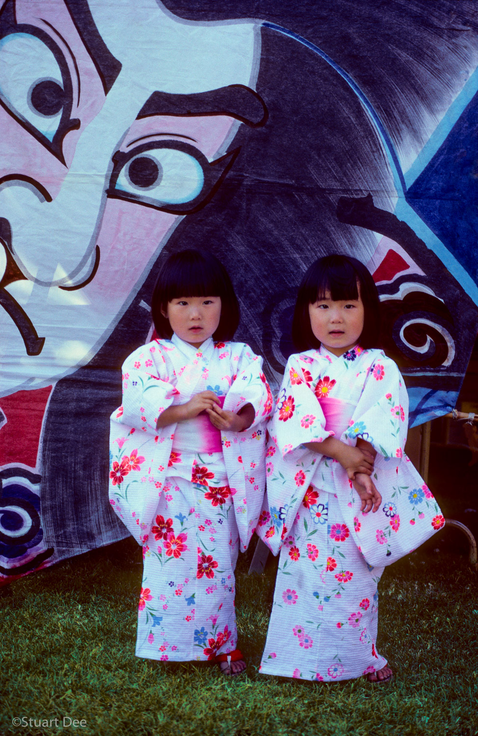 Twin Japanese girls at a Japanese festival, with a large picture of Japanese face staring at them from the background.