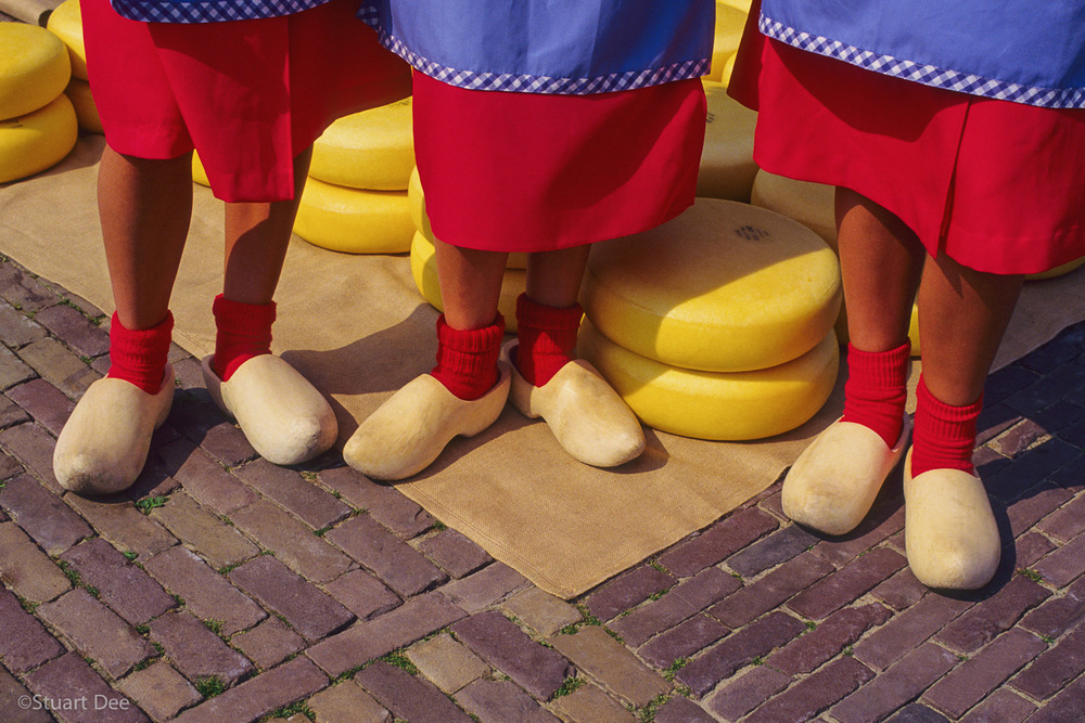 Three young Dutch women wearing wooden clogs, in front of cheese, Alkmaar Cheese Market, Alkmaar, Holland  The Alkmaar Cheese Market is unique in the world.