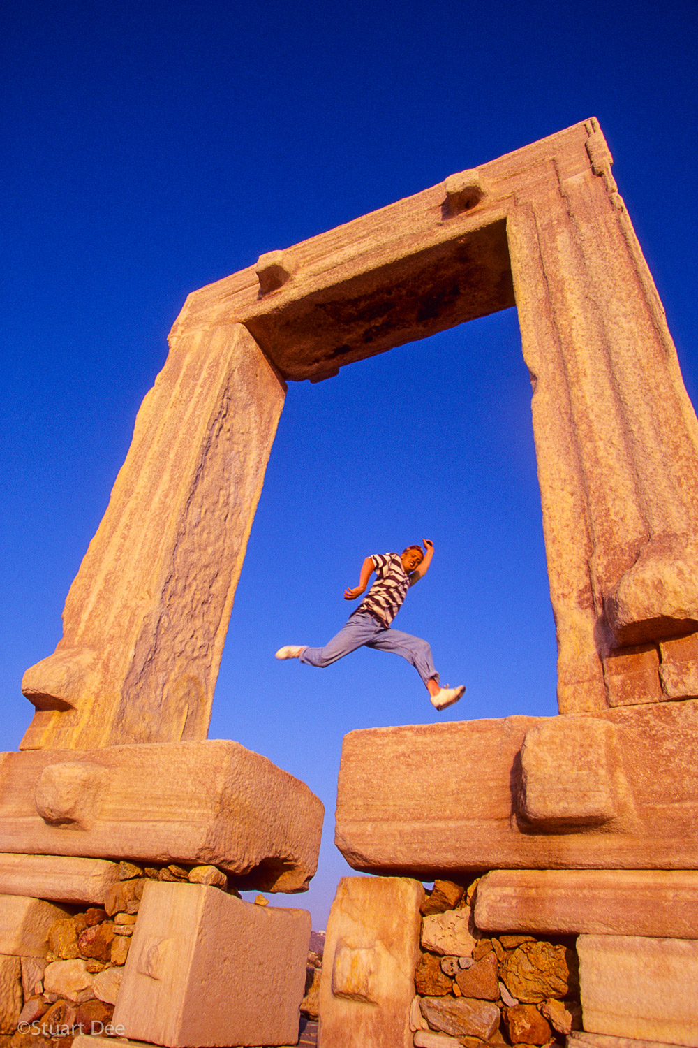 Man jumping over a gap in the marble stones of the Portara at sunset.  The symbol of Naxos, the portara is the gate of the unfinished Temple to Apollo, Naxos, Greece
