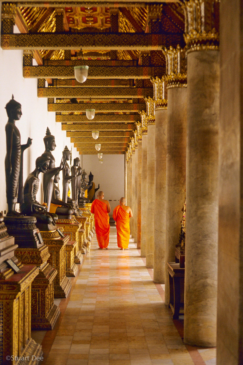Two Buddhist monks walking down hallway, Marble  Temple,  Bangkok, Thailand
