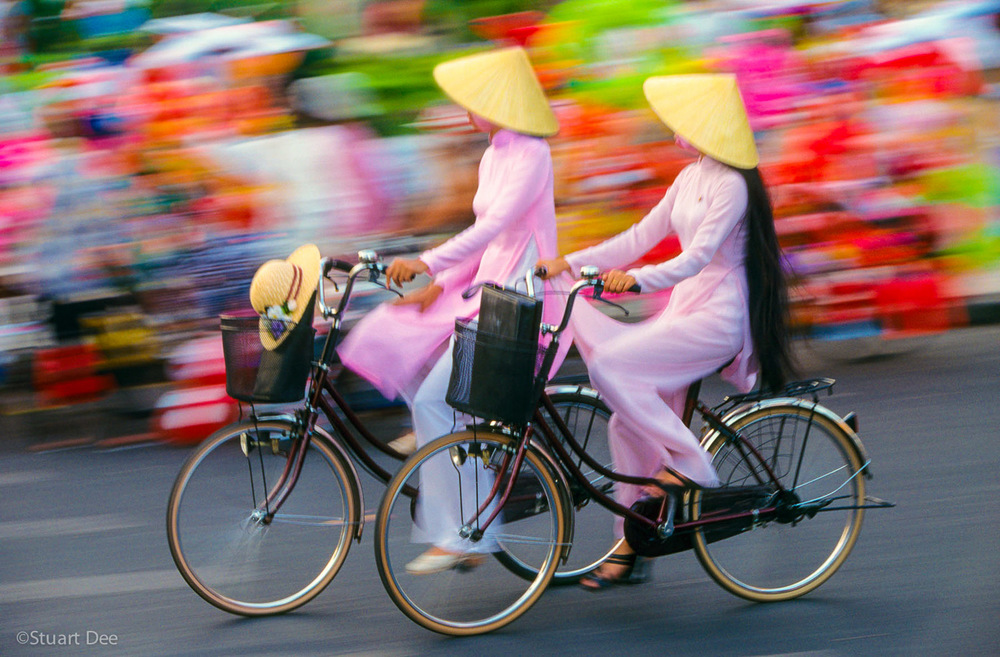 Two women wearing ao dais, on bicycles,  Ho Chi Minh City, Vietnam