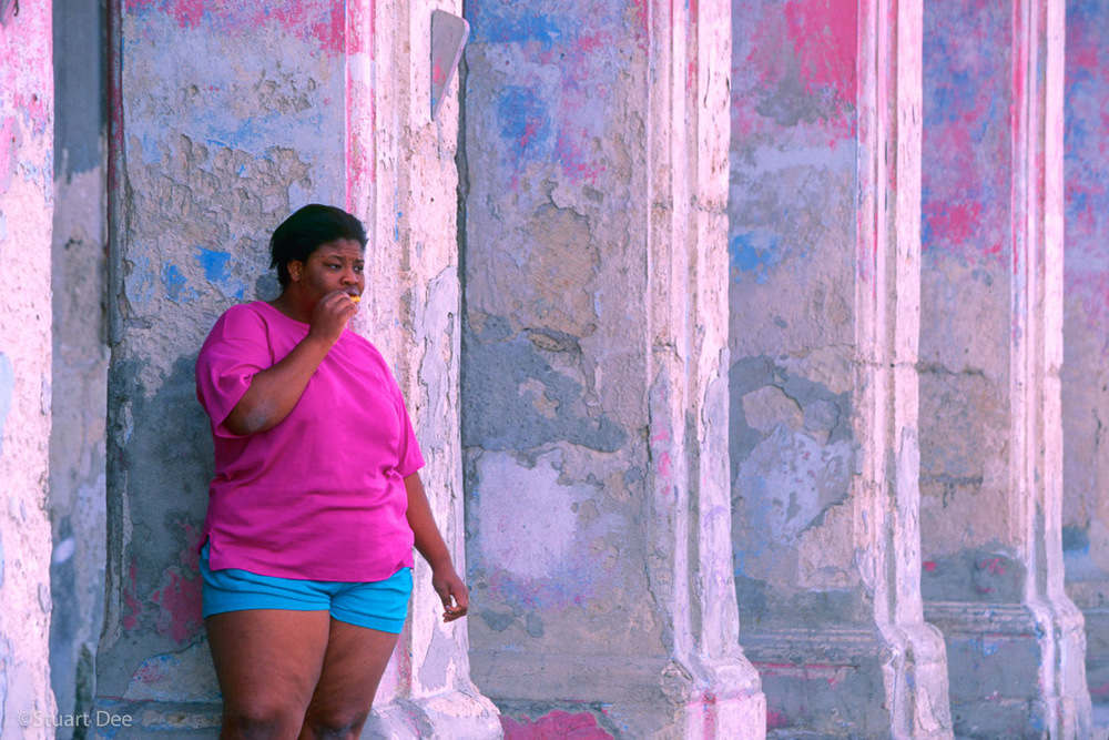 Obese woman standing among columns of an old building with chipped pink and blue paint, Malecon, Havana, Cuba