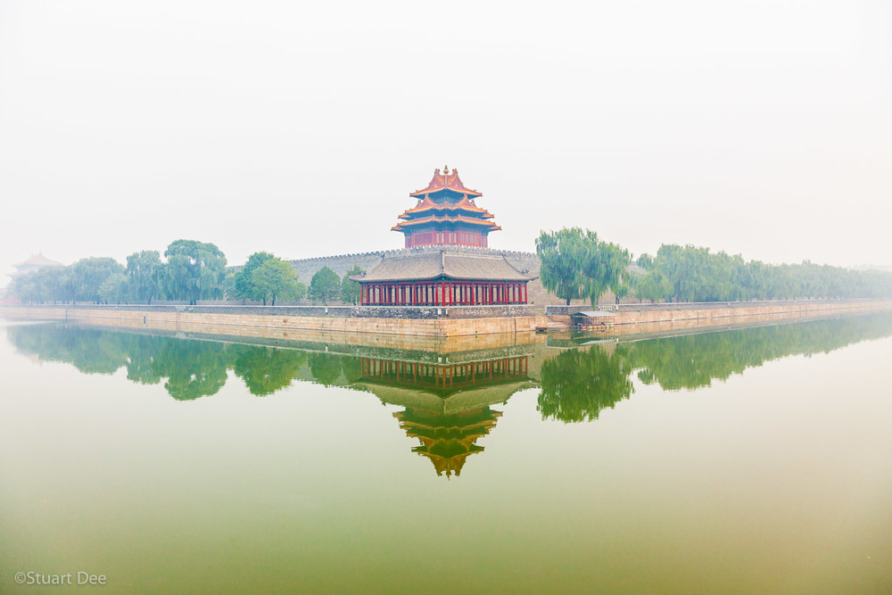 Watchtower of Forbidden city in fog, reflected in moat, Beijing, China