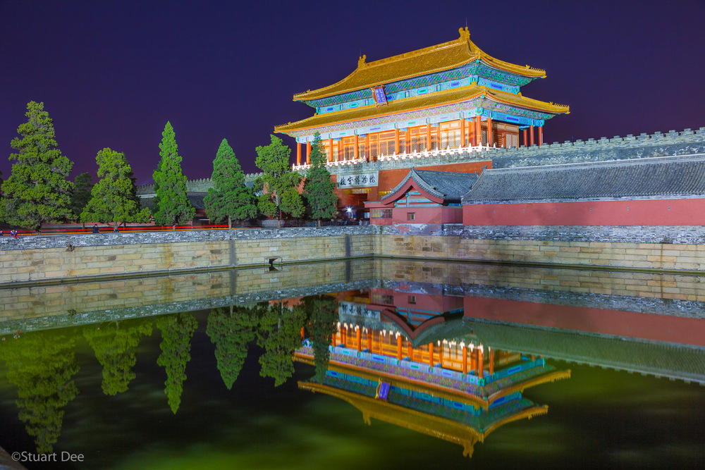 The Gate of Divine Might at night, reflected in the moat, Forbidden City, Beijing, China