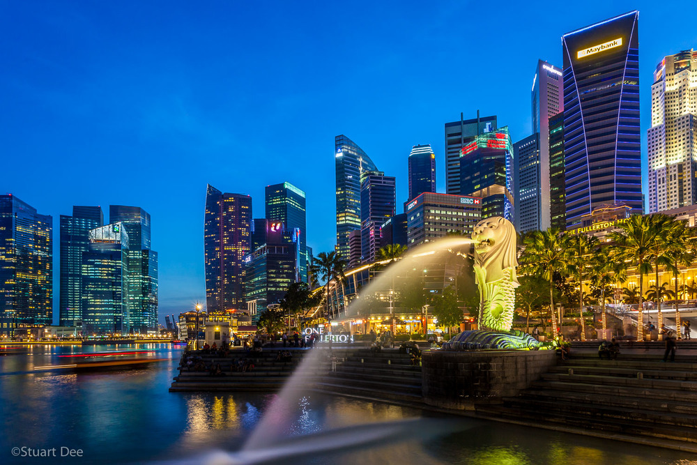 City skyline, Marina Bay, and Merlion Park  at dusk/night, Singapore.