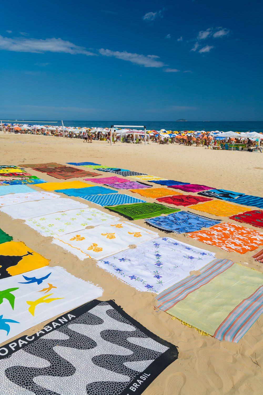 "Colorful beach towels on the sand, Ipanema Beach, Ipenema, Rio de Janeiro, Brazil. This beach is one of the most famous in Rio, and was immortalized with the Bossa Nova song ""The Girl from Ipanema."""