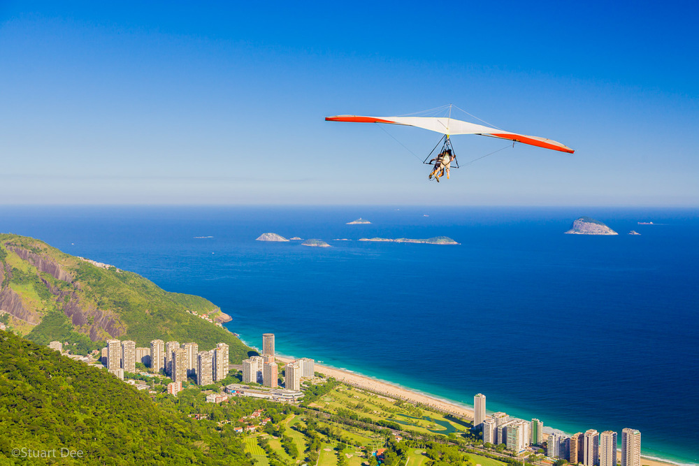 Hang gliders taking off from the Pedra Bonita Ramp and flying over the Tijuca Forest, Gavea Golf Course, and Sao Conrado, Rio de Janeiro, Brazil