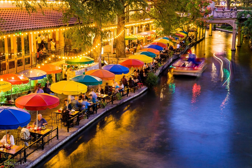 People dining at outdoor terrace at the San Antonio Riverwalk at sunset/dusk/evening/night, San Antonio River Walk, San Antonio, Texas, USA. The River Walk is the most popular tourist atrraction in the city.