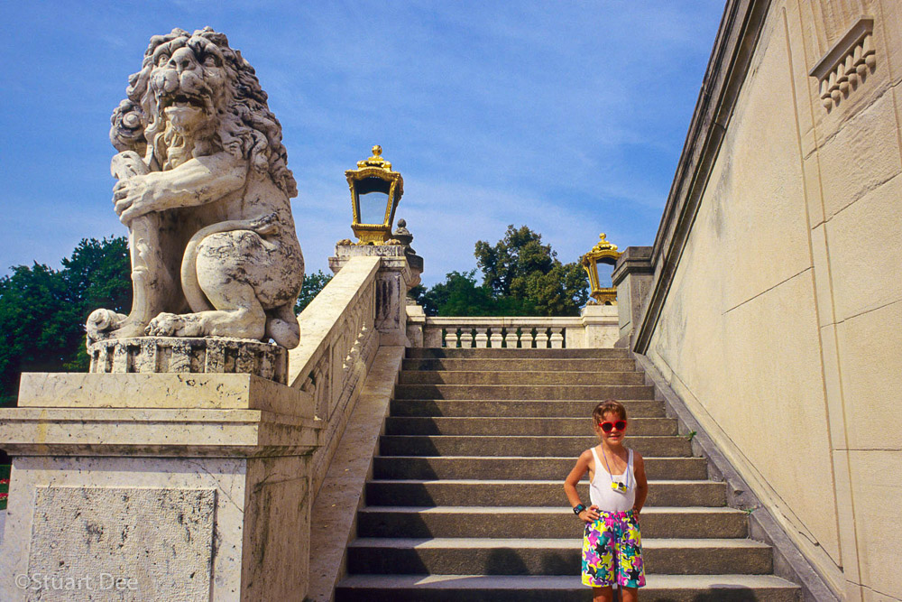 A young tourist poses in front of the steps of Nymphenburg Palace, Munich, Germany.