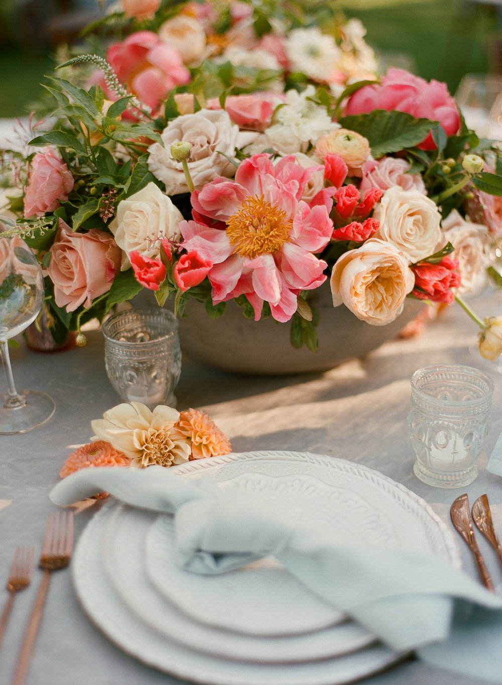 Photography  . Christina McNeill.   The added touch of flowers on the tables was the planner's idea. And it's a good one.  I love the way the china, the flatware and that knotted napkin worked together with those Peonies and dahlias.   Executing this event with one team member down was harder than I could have imagined because of the extreme heat but getting there early is a key for getting things done on time.  You need extra time when the weather is hot because everyone slows down a little, when the space is vast(trying walking in all black clothing with two garlands down 200 yards to the golf course when it's over 105), when the elements are against you.