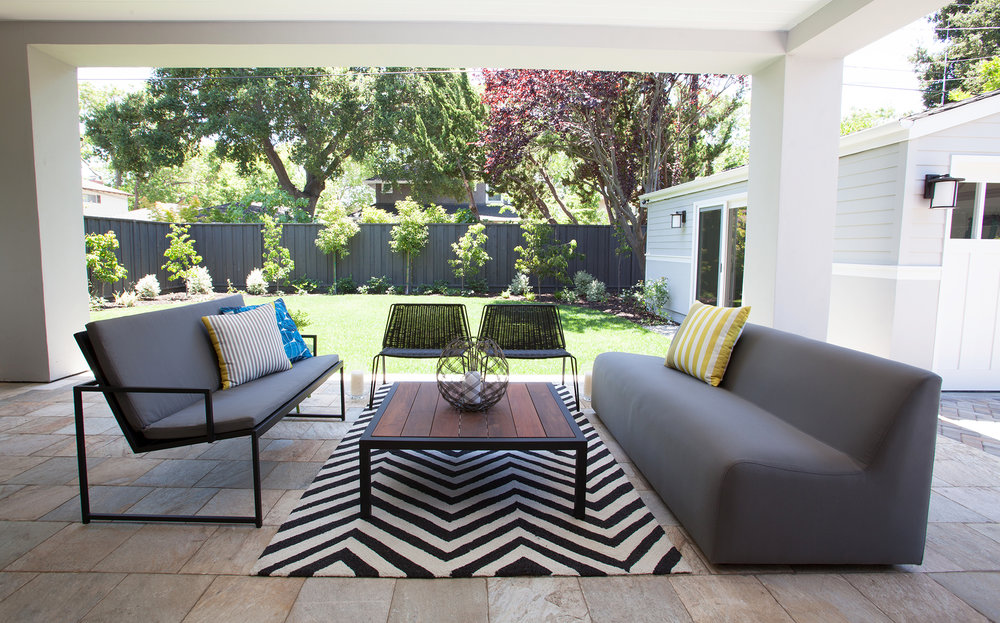 Large accordion windows from the living room open up to the outdoor patio and beautifully landscaped backyard. The seating is ample with a highlight of two modern low black chairs made of durable plastic woven across a powder coated frame. A bold black and white chevron area rug connects back to the interior.