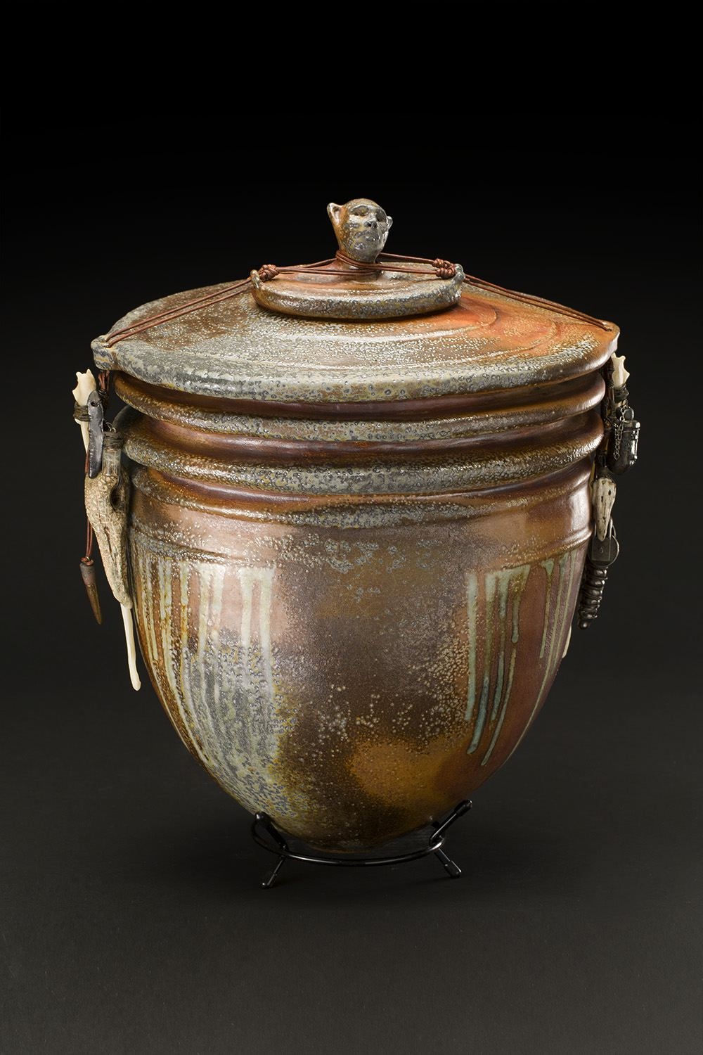 Melanie Ferguson    Battles Left Behind  , 2016 Hand built lidded vessel; stoneware, flashing slip, glaze, oxide stains, gas fired in soda, bone, glass, dandelion seed, wire, silver, leather 17 x 13.5 x 10 inches 43.2 x 34.3 x 25.4 cm MFe 34