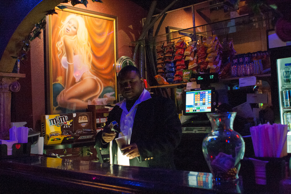 Matty, a bouncer at a strip club, pours soda for a customer. This is an all-nude club where no alcohol is permitted by law.