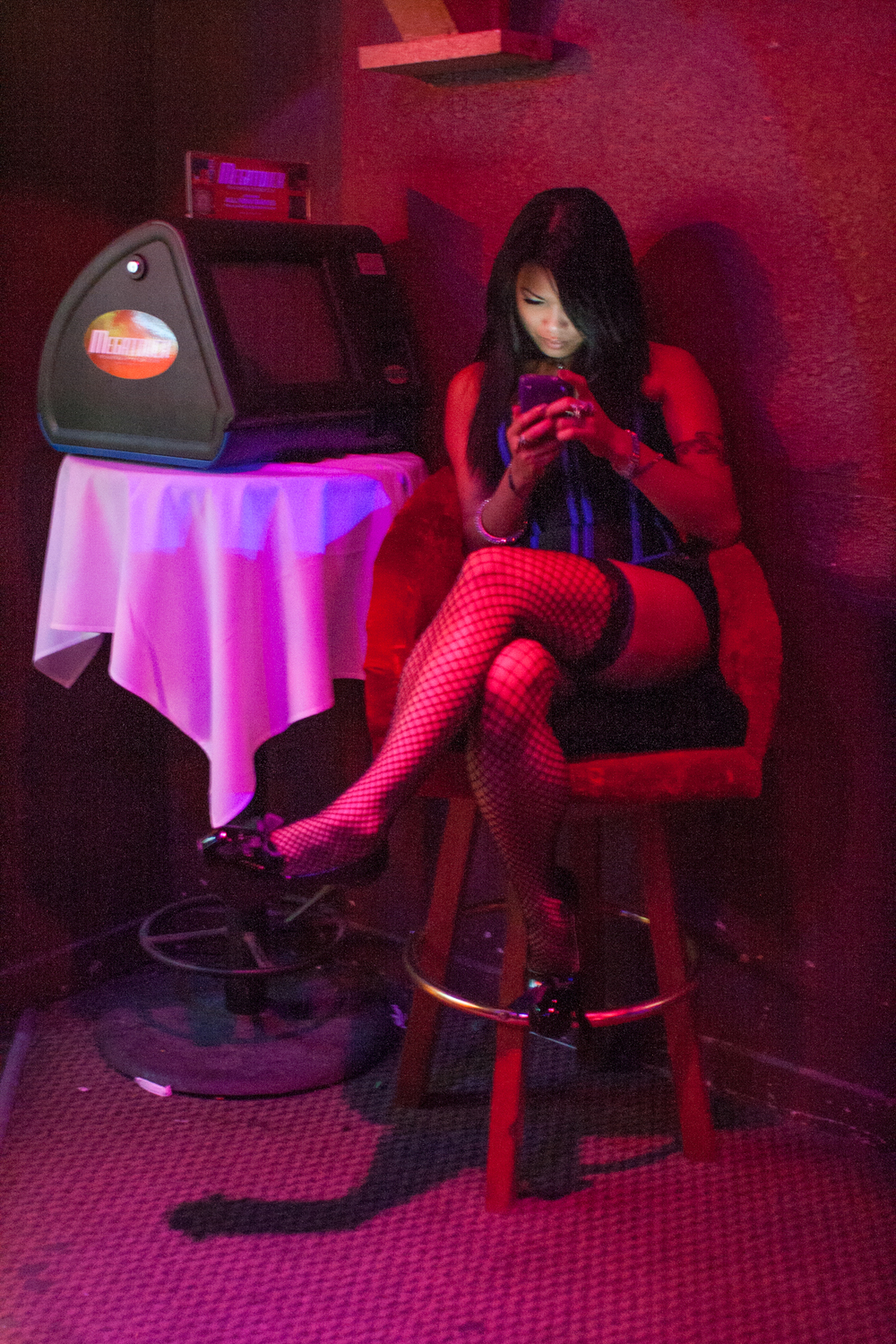 Jade on her phone during her downtime at the strip club where she works