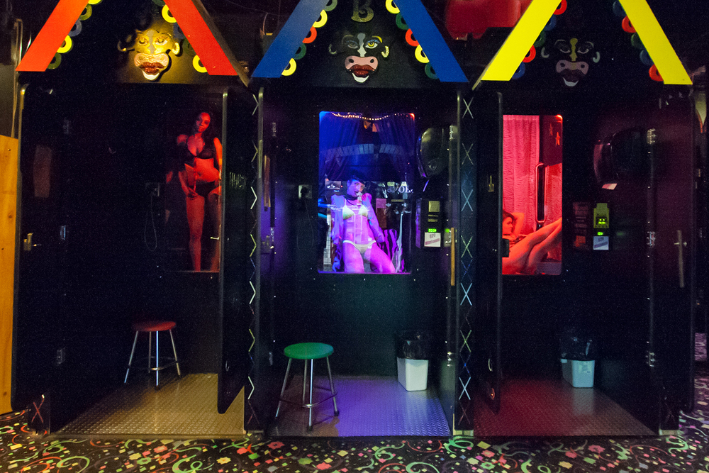 "Entrance to a live peep show, where customers pay to sit in private booths with girls who perform behind glass. ""Shows"" cater to a customer's specific fantasies or fetishes, and may include stripping, sex toys, and /or conversation via a telephone that connects them."