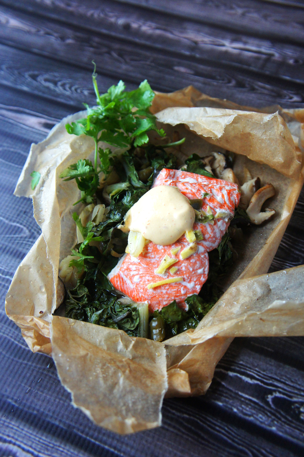 Salmon and Shiitake Mushrooms with Greens in Parchment, topped with Sriracha Aioli. A paleo-friendly dish