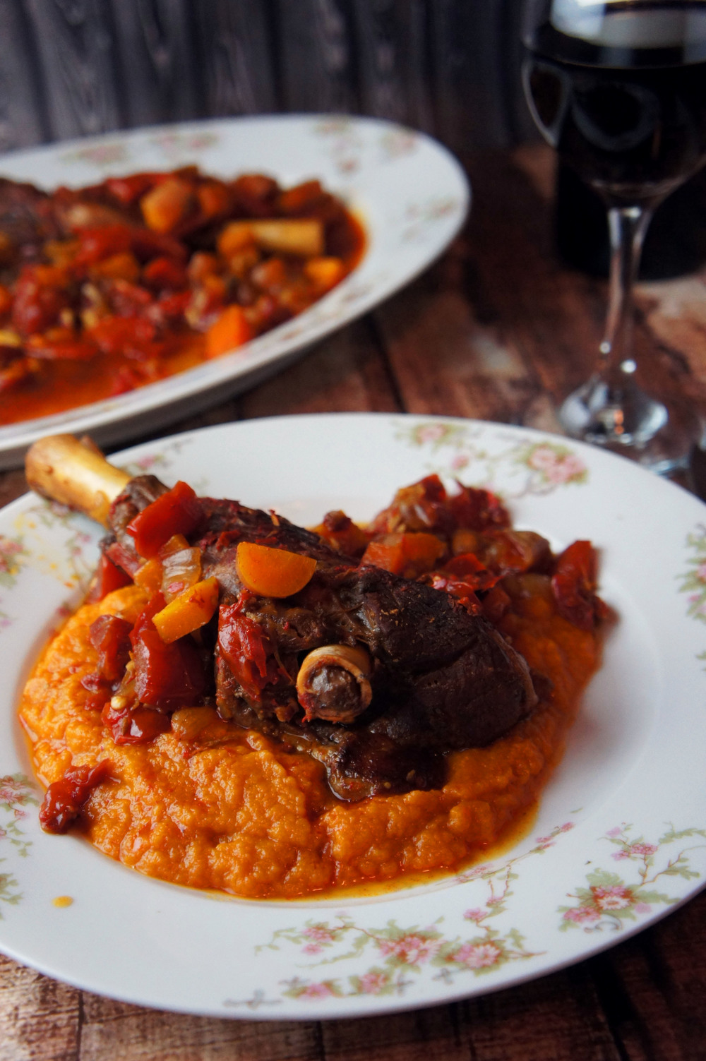 Harissa Goat Shank in the slow cooker with tomatoes, carrots, and butternut squash puree. A paleo dish with middle eastern flavors that can be done in the slow cooker.