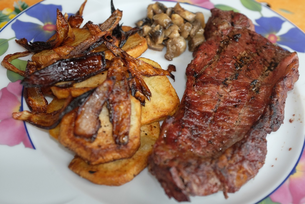 Charcoal fried steak with fried  potatoes and onions