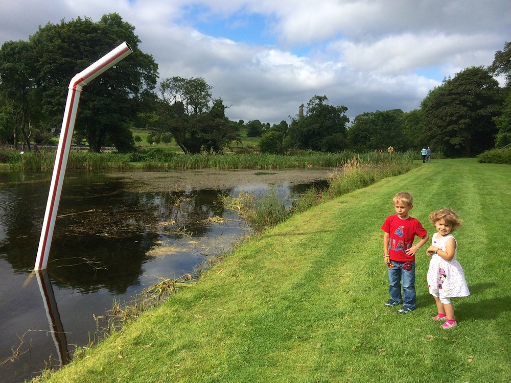 "Kian trying to slurp up the lake with the straw - ""The installation of the straw sculpture is intended to highlight the current issue of water charges and water equality in Ireland. The placement of the straw in the lake should remind people where their water comes from and how much of it is left"". -Paul O'Driscoll (Artist and Musician in Mayo)"