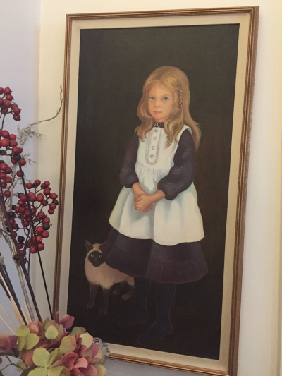 "My mom's painting of me with my first cat, Charlie, the ""hairy, little man."""