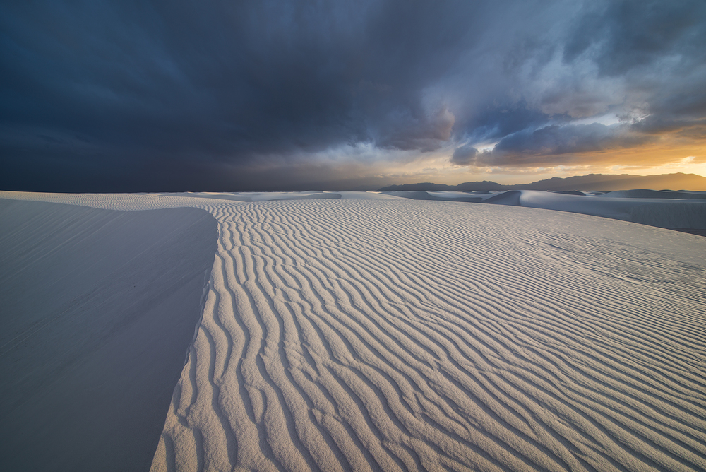Storm clouds break near sunset send beautiful light across a rippled sand dune.