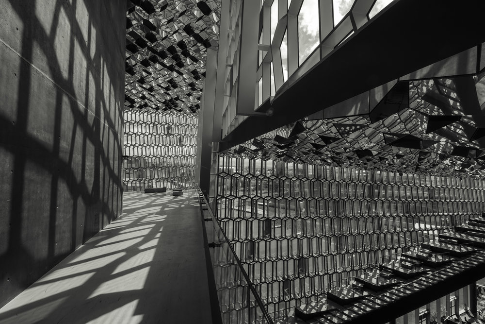 A walkway along the buildings core reflects patterns of light and shape from the windows.