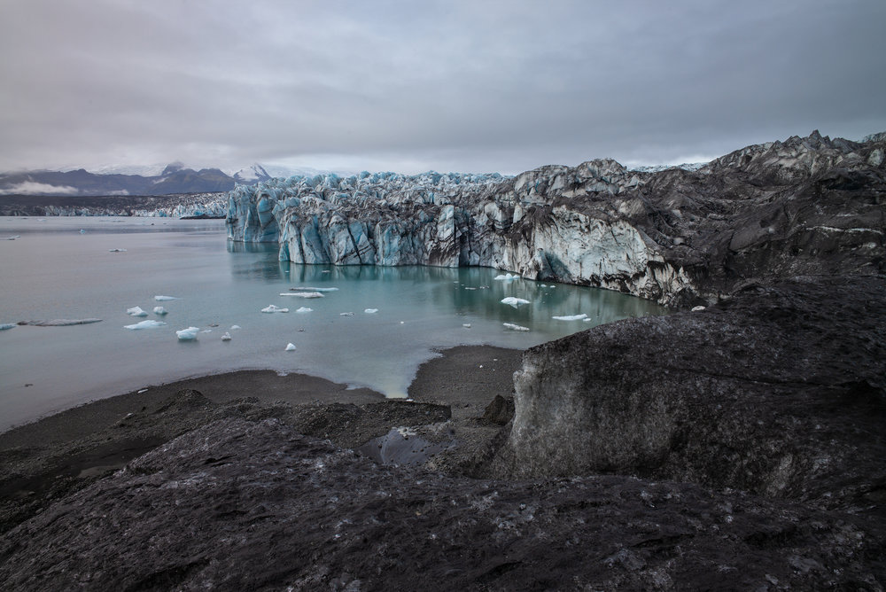 Ash covered ice gives way to the ice calving site and the blue waters of the glacial lagoon.