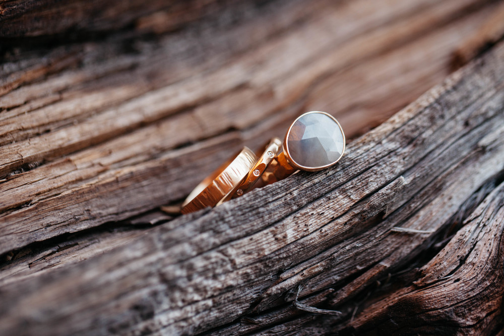 Rings by Leslie & Jared: 18k yellow gold; 4mm textured flat band, 2.5mm faceted half round band with flush set diamonds, and organic shaped rose cut sapphire on a hammered band.  Photo by Tim Kressin