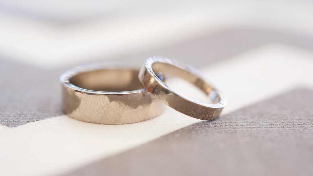 Rings by Ryan & Kristina; 5mm and 3mm flat bands in palladium white gold with a light hammered texture.  Photo by Barbie Hull