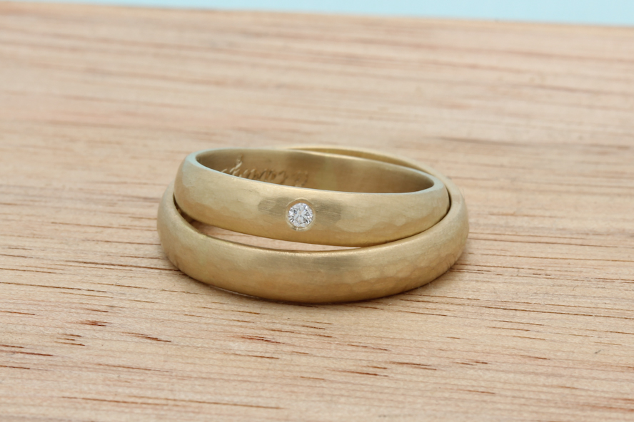 Caterina and Ben's classic bands with a hammered texture around the center and a brushed finish in 18k yellow gold. Hers is flush set with a diamond.