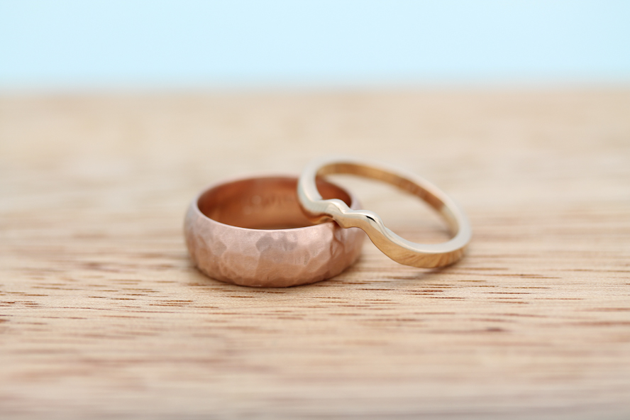 Laura and Scott's rose gold and peach wedding bands. His rose gold ring with a carved texture. Hers is peach gold, carved to compliment her vintage engagement ring.