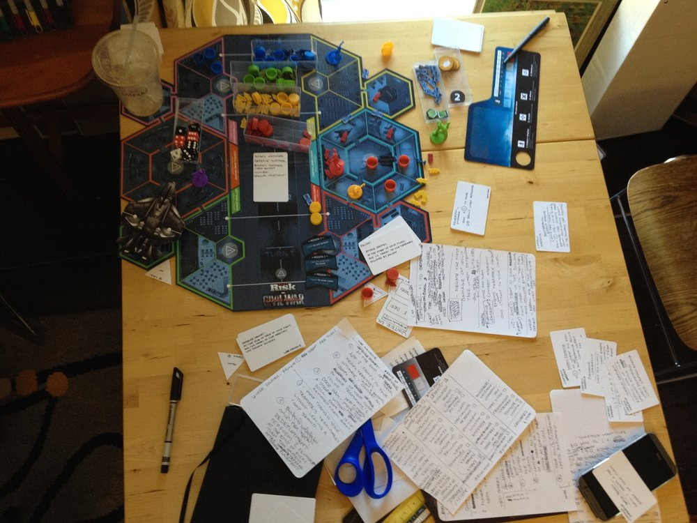 "Detailed notes were captured during each play session as a form of version tracking. New features and rules were tested and compared to previous versions of the game. At the end of the game, mechanics like player to player interaction, player decision, and luck vs. skill are analyzed. In this particular playtest, I introduced a player decision in the form of ""breach points"" -- this triangular piece is slid into a location around the game board at the beginning of the game and becomes the 'spawn location' of a player's troops for the remainder of the game. This solved an issue of randomized placement of troops into any room of the player's choosing which was causing a game balance issue."