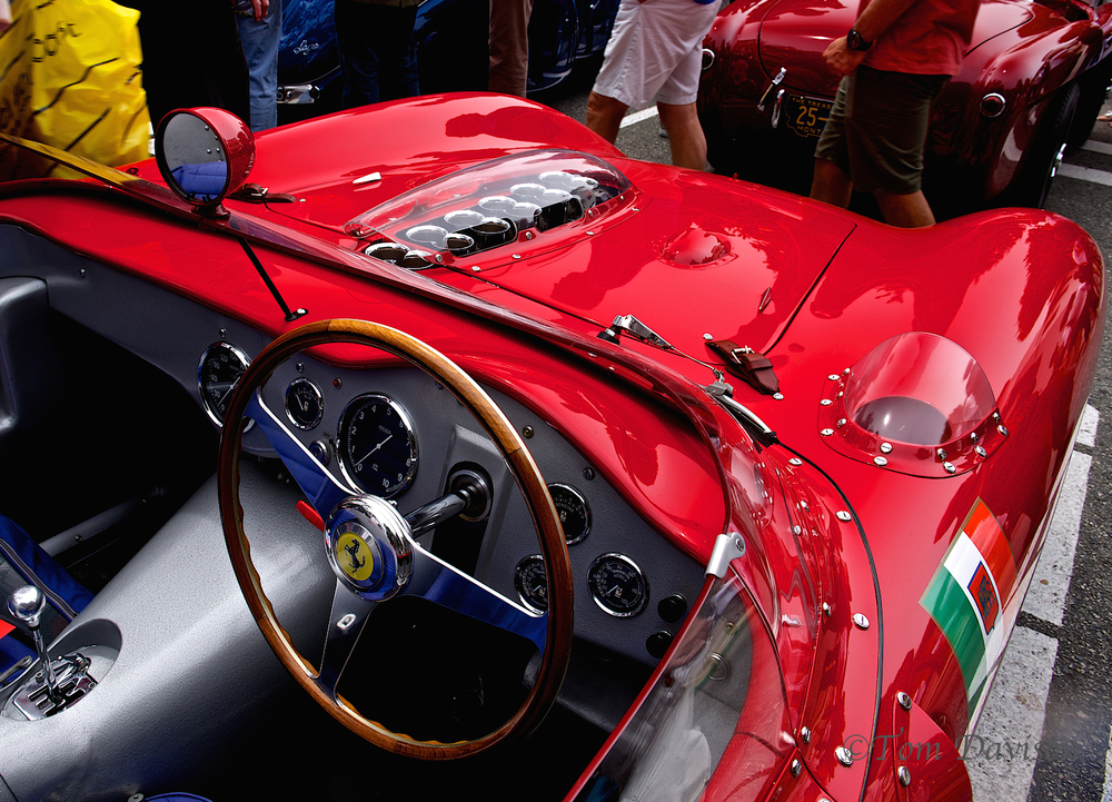 Not just another red car. Leather straps, a real convertible with an interesting take on a rear view mirror . . .