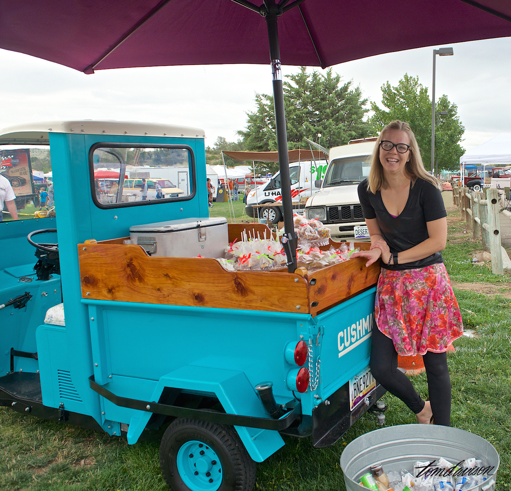 This young lady's Dad is a member of the Prescott Antique Auto Club and he enjoys restoring old Cushman vehicles like this three wheel mini hauler. She was using it to offer her specialty baked goods!