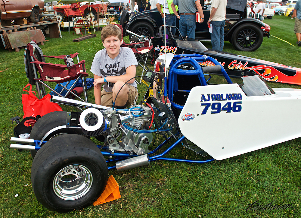"This is twelve year old AJ with his dragster. He races and wins at National Championship events. He accelerates to 80 MPH while reaching the end of the 1/8 mile course in less than 8 seconds! He admitted than he had been beaten (once) by his ten year old sister Lindsay in her own dragster, seen in the background, called ""Daddy's Girl""."