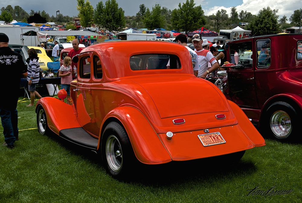 1934 Ford coupe, with background showing the diversity of the attendees.