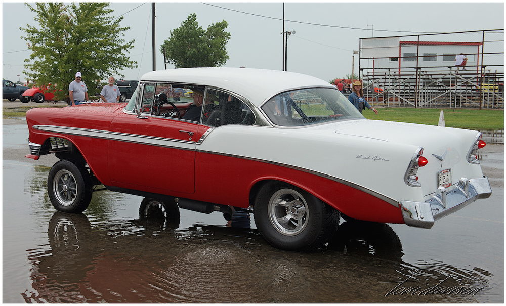 A perfectly restored 1956 Chevy Bel Air re-imagined as a racer.  This photo shows how much the heavy rain had fallen in the morning just prior to the opening of the event.  The skies started to clear and the crew worked hard to get the race track dried off so cars could race.  It turned out to be a beautiful day.