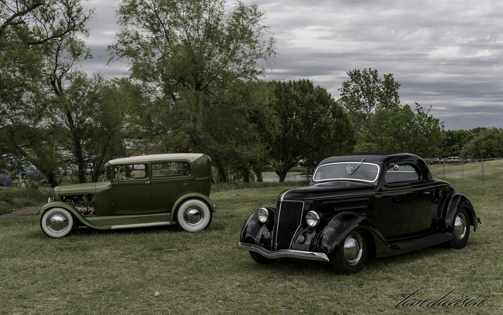Green is a Model A sedan and the black car is a 1936 Ford three window.
