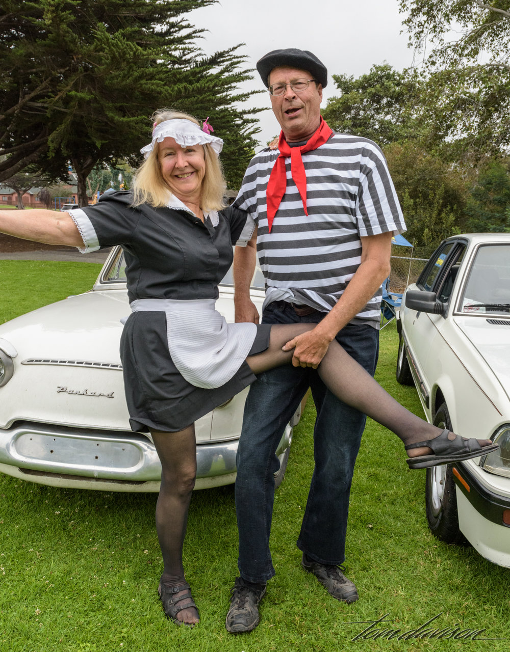 They were asked if they would be willing to pose in front of their car.  Of course! His t-shirt is a white Walgreen's 'special' that he put tape on in stripes, spray painted the open stripes and then pulled the tape off.