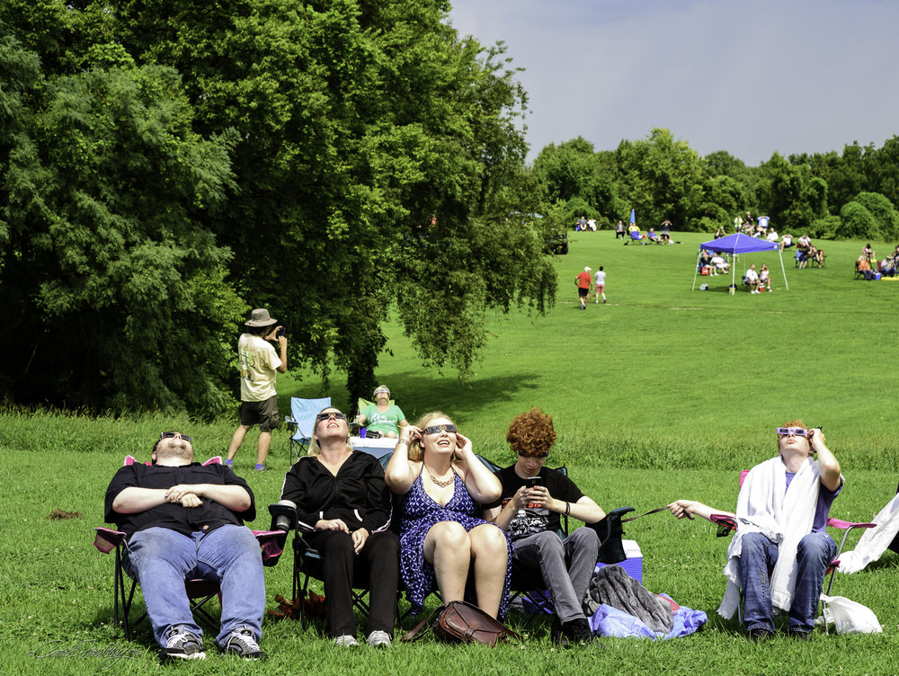 Finally, the sun came out and the eclipse started. This was a common scene. People were either looking up or on their phone. The lady on the right had brought her dog and its leash is what she is holding. The gentleman on the far left never moved. He may have slept through the entire event!